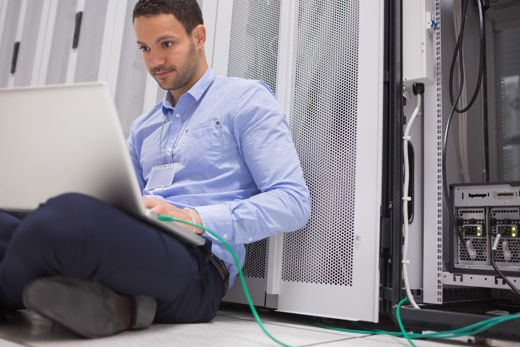 Man concentrating on laptop connected to server in data center